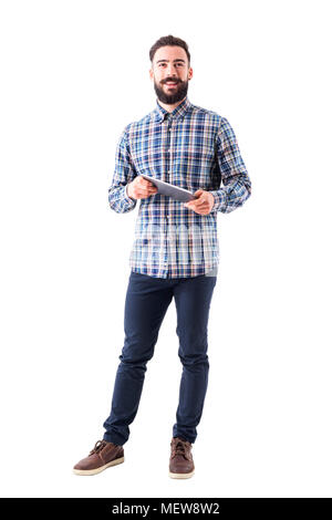 Happy smiling modern business man holding tablet computer looking at camera. Full body length portrait isolated on white background. - Stock Photo
