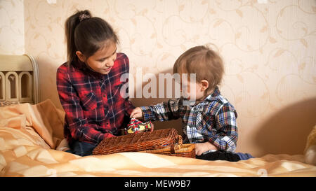 Teenage girl playing with toddler boy on bed at bedroom - Stock Photo