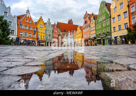 Traditional colorful gothic houses in the Old Town of Landshut, historical town in Bavaria by Munich, Germany, reflecting in a rain puddle - Stock Photo