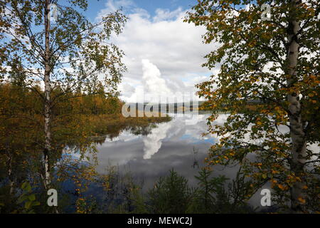 Cumulus clouds are towering over a lake in autumn. The forest on the shore is reflected in the still water. - Stock Photo