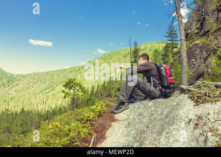 young man with a backpack sits on a rock in the mountains view. - Stock Photo