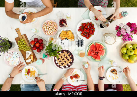 Friends having outdoor meal eating fruit, pie, cheese and drinking coffee in the garden - Stock Photo