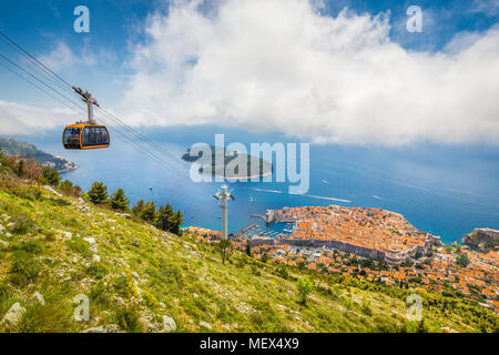 Aerial panoramic view of the old town of Dubrovnik with famous Cable Car on Srd mountain on a sunny day with blue sky and clouds in summer, Croatia - Stock Photo