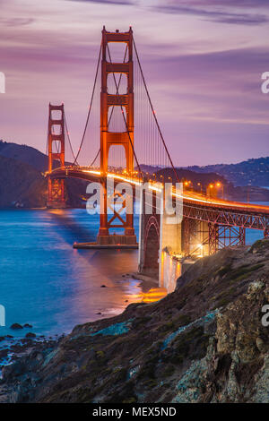 Classic panorama view of famous Golden Gate Bridge seen from scenic Baker Beach in beautiful post sunset twilight with blue sky and clouds at dusk - Stock Photo