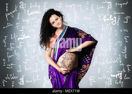 studio portrait of a pregnant woman in Indian sari, a pregnant belly painted with henna - Stock Photo