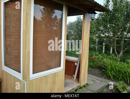 Glass doors and Windows in a wooden veranda. Entrance to the country house - Stock Photo