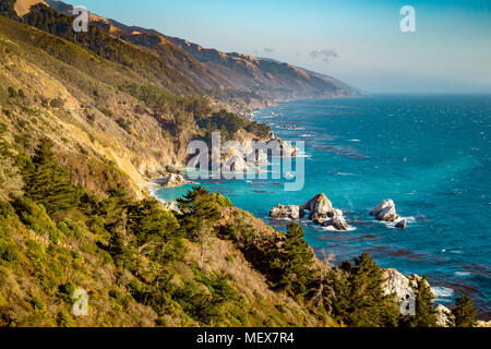 Scenic view of the rugged coastline of Big Sur with Santa Lucia Mountains along famous Highway 1 illuminated in evening light at sunset, California - Stock Photo