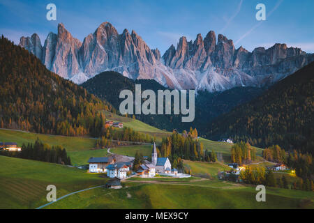 Beautiful view of idyllic mountain scenery in the Dolomites with famous Santa Maddelana mountain village in beautiful golden evening light at sunset - Stock Photo