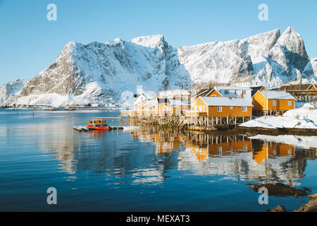 Scenic Lofoten Islands archipelago winter scenery with traditional yellow fisherman Rorbuer cabins in the historic village of Sakrisoy, Norway - Stock Photo