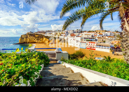 Stairs from cliffs leading to sandy beach  surrounded by white architecture of Carvoeiro, Algarve, Portugal - Stock Photo