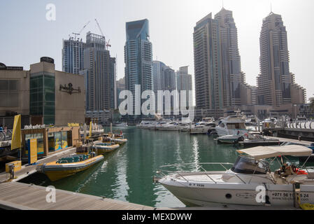 A cityscape view of the tall buildings surrounding Dubai marina with boats moored in the foreground - Stock Photo