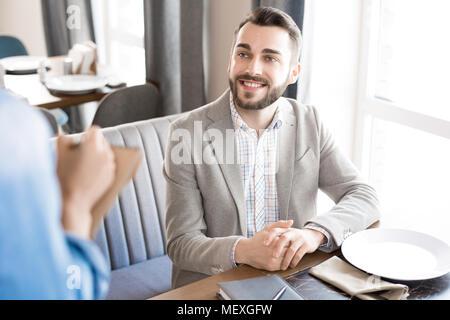 Cheerful businessman making order in restaurant - Stock Photo