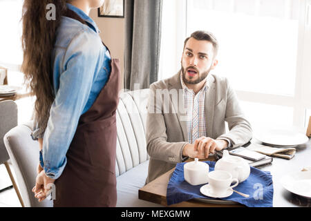 Pensive customer asking waitress in cafe - Stock Photo