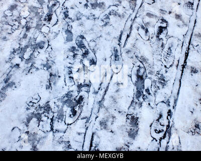 A lot of fresh footprints and tracks on the snowy ice winter background - Stock Photo