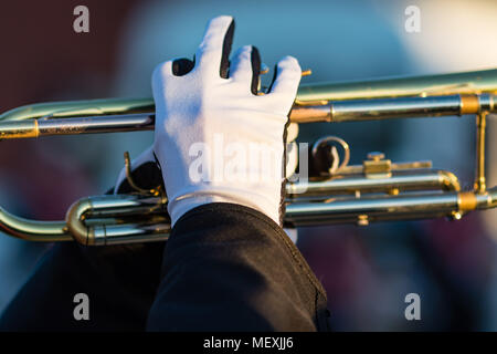 the gloved hands of a trumpet player in a marching band - Stock Photo