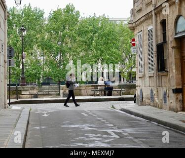 Couple sitting on bench along Seine while man walks behind them, reading a sheaf of papers. Ile Saint-Louis, Paris, France. - Stock Photo