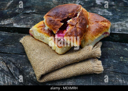 Freshly baked pies with berries (raspberries, apples, cherries) on the wooden table. Village style. - Stock Photo