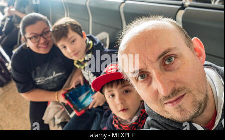 A family selfie taken in the departure lounge of an airport. - Stock Photo