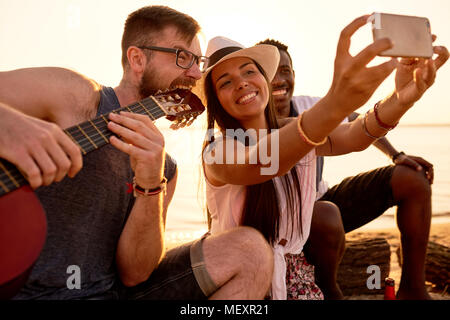 Smiling friends photographing with crazy musician on beach - Stock Photo