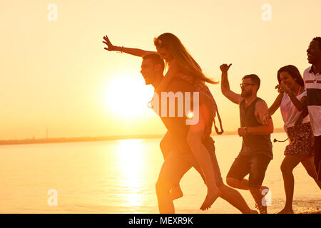 Hilarious friends running on water in light of sunset - Stock Photo