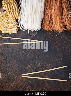 Different Asian rice noodles on rusty background - Stock Photo