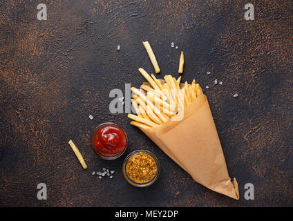 French fries in a paper bag with sauces - Stock Photo