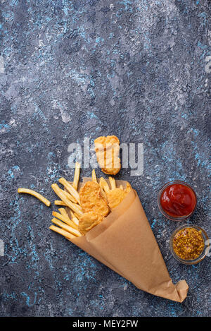 Fish and chips with tomato sauce and mustard - Stock Photo