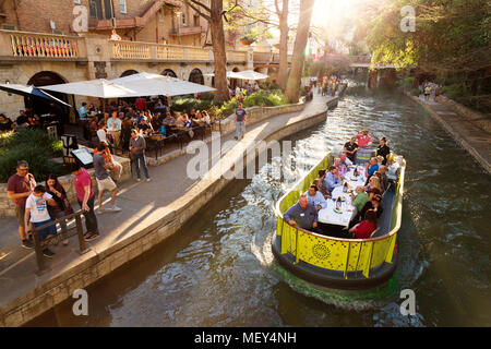 Travellers dine on a barge on the San Antonio river; San Antonio River Walk, San Antonio, Texas USA - Stock Photo