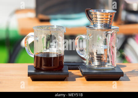 Making pour over coffee at the street market. Glass cups with dripper and filter - Stock Photo