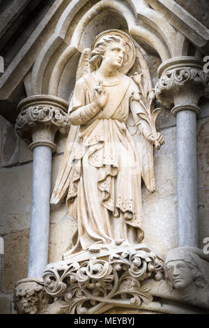 Sculpted stone statue of an angel on the exterior west wall at the medieval cathedral of Salisbury, England. - Stock Photo