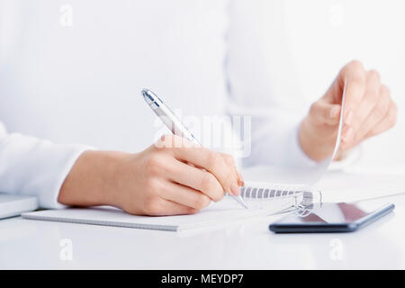 Close-up shot of businesswoman's hand writing something while sitting at office desk. - Stock Photo