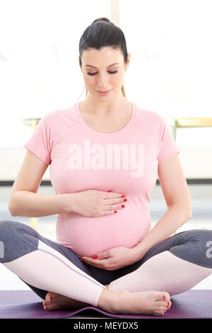 Full length shot of pregnant young woman performing a yoga routine to relax at home. - Stock Photo