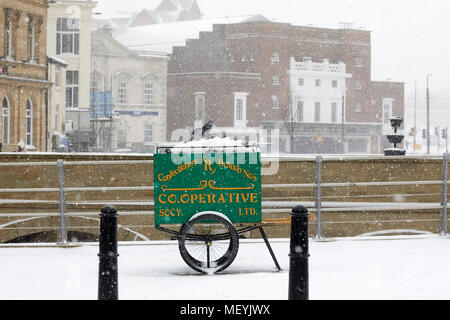 Winter snow ai Rochdale Lancashire. Cooperative hand cart on display in the town centre used as a planter - Stock Photo