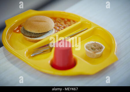 A school dinner meal tray with burger, beans, cake and drink - Stock Photo