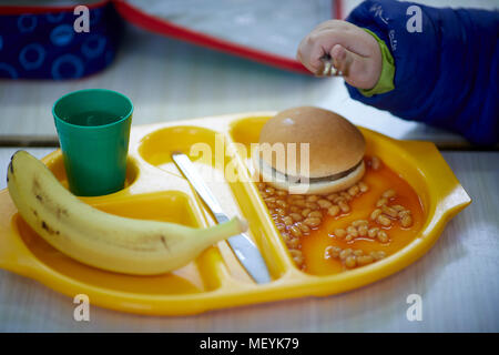 A school dinner meal tray with burger, beans, fruit banana and drink - Stock Photo