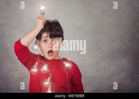 surprised boy with light bulbs on gray background - Stock Photo