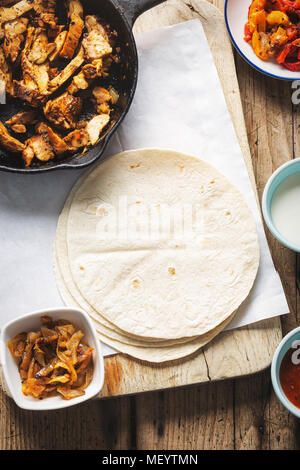 Chicken fajitas. Marinated chicken pieces with red and yellow peppers and onions with tomato salsa, sour cream and tortilla wraps - Stock Photo