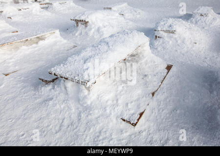 Wooden benches and desk on restaurant terrace barely visible under heavy load of snow. Concept illustrating extreme snowfall. - Stock Photo