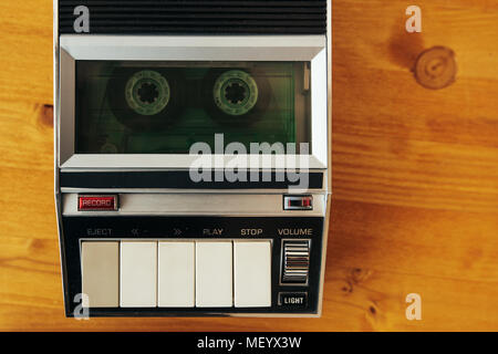 Audio cassette tape rolling in vintage player on the desk, top view. Police interrogation sound recording retro technology concept for 1970s, 80s and  - Stock Photo