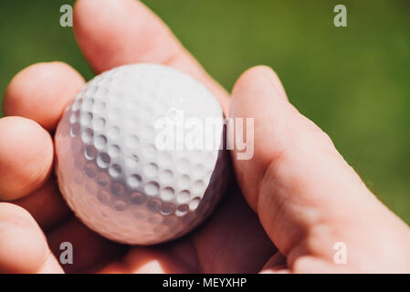 Golfer holding golf ball, close up of male hand - Stock Photo