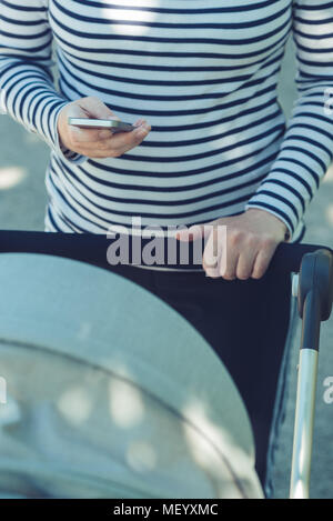 Mother using mobile phone while pushing baby stroller on the street, selective focus - Stock Photo