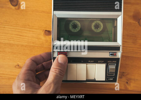Finger pressing record button on vintage audio cassette tape player, top view. Police interrogation sound recording retro technology concept for 1970s - Stock Photo