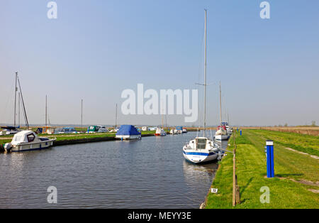 A staithe with moored boats off the River Bure on the Norfolk Broads at Oby, Norfolk, England, United Kingdom. - Stock Photo