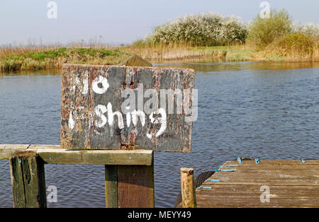 A worn No Fishing sign by the River Thurne on the Norfolk Broads at Thurne, Norfolk, England, United Kingdom, Europe. - Stock Photo