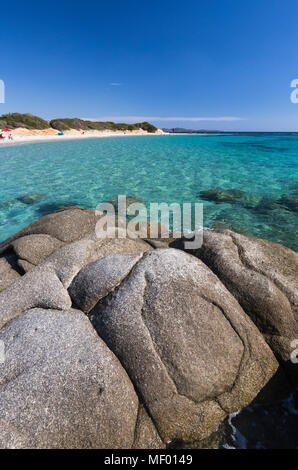 Rocks frame the turquoise water of sea around the sandy beach of Sant Elmo Castiadas Costa Rei Cagliari Sardinia Italy Europe - Stock Photo