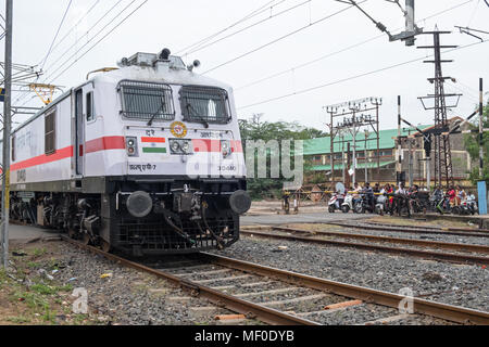 Pondicherry, India - March 17, 2018: A locomotive at the front of a passenger train passing over a level crossing outside the main station - Stock Photo