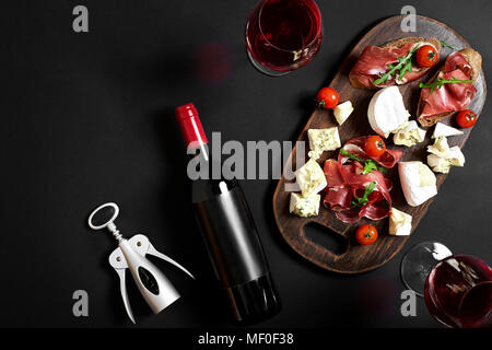 Delicious appetizer to wine - ham, cheese, baguette slices, tomatoes, served on a wooden board, and glass with red wine on black surface - Stock Photo
