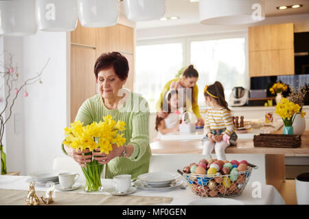 Senior woman arranging flowers on dining table with family in background - Stock Photo