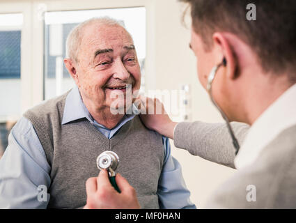 Senior man smiling at nurse with stethoscope at home - Stock Photo
