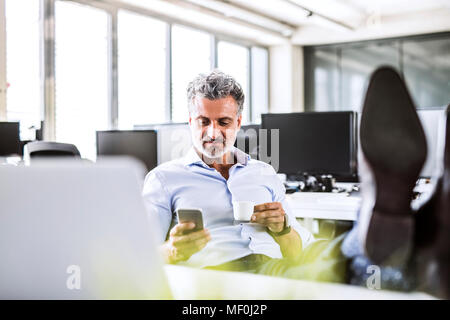 Relaxed mature businessman sitting at desk in office using cell phone and drinking coffee - Stock Photo